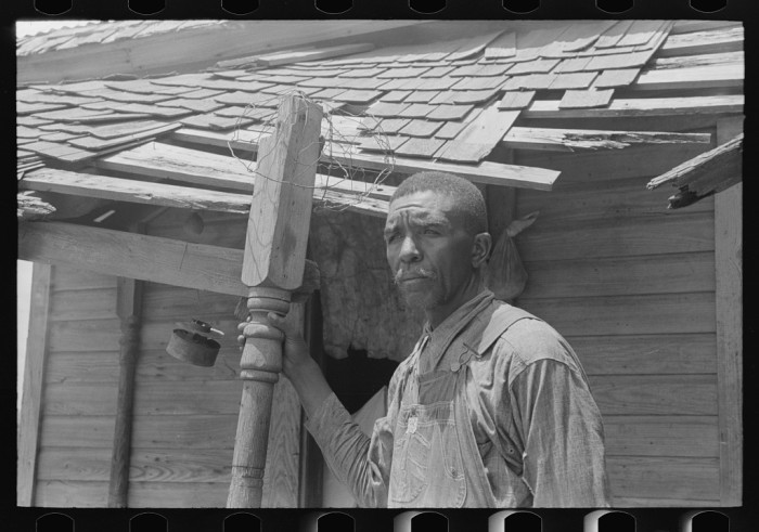 18. A tenant farmer on his front porch. The man said that the owner/agent changed so often that no one ever took any interest in the condition of the land or buildings. This photo was taken south of Muskogee in 1939.
