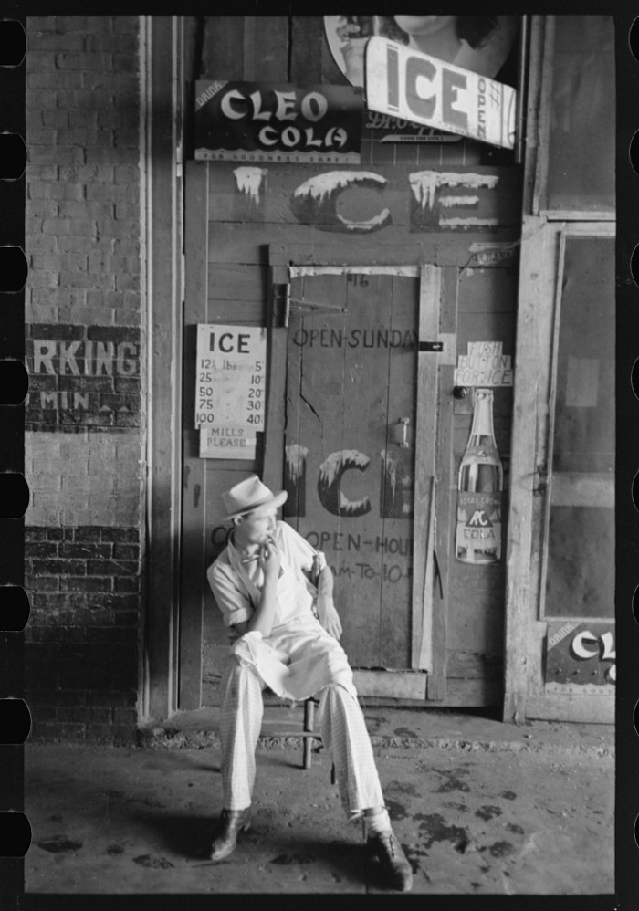 19. This man is sitting in front of a small icehouse in Muskogee, 1939.