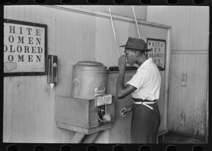 """23. This man is drinking at the""""Colored"""" water cooler in a streetcar terminal in Oklahoma City in 1939."""