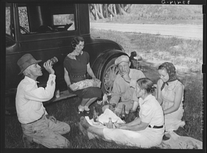 """7. A migrant steeple-jack and his family eating a """"bought lunch"""" by the roadside near Prague in Lincoln County in 1939."""