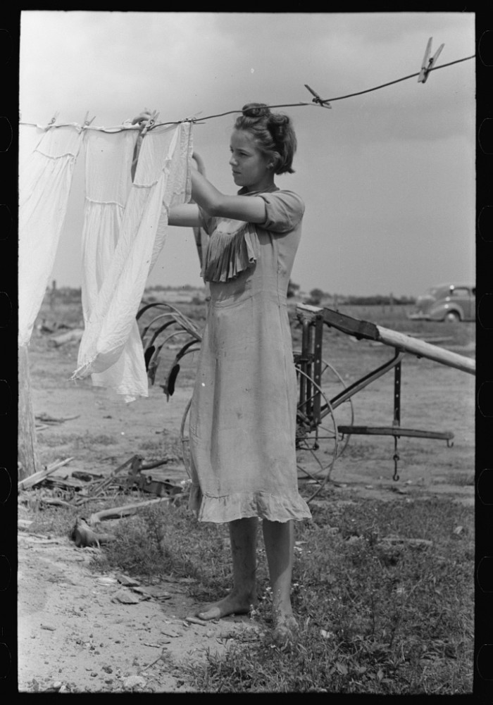"1. ""Daughter of tenant farmer hanging up clothes near Warner, Oklahoma."""