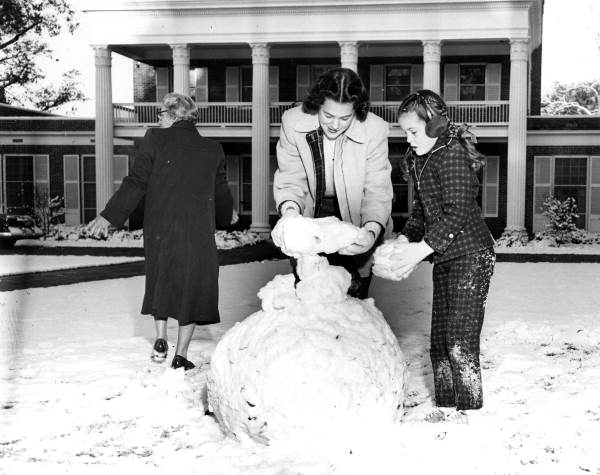 Governor's daughters Mary Call and Darby Collins build a snowman on the mansion lawn