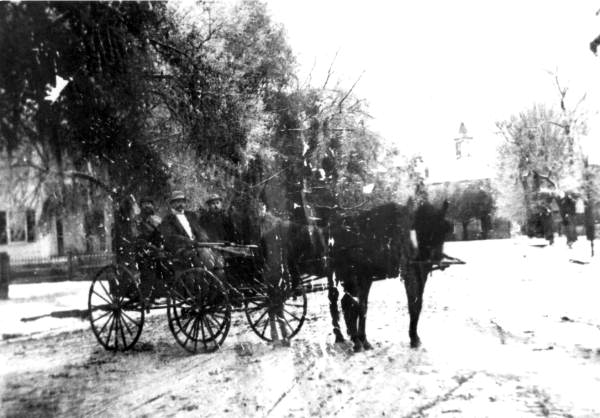 Men in horse-drawn wagon in a snow storm