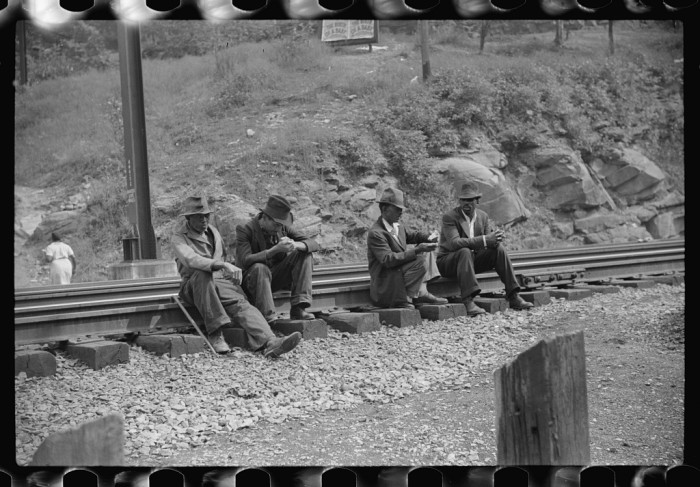 9. These men are sitting around by the railroad tracks in the mining town of Davey in 1938.