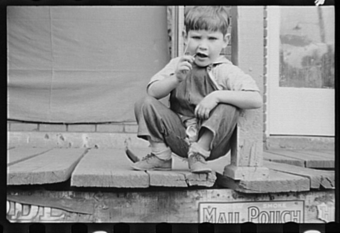 14. This little boy was sitting on a porch in Omar in 1935.