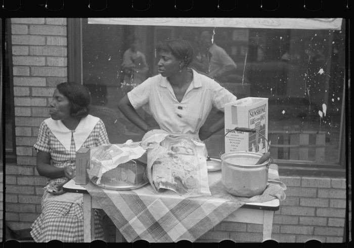 5. These women are selling cake on the sidewalk in Scotts Run.