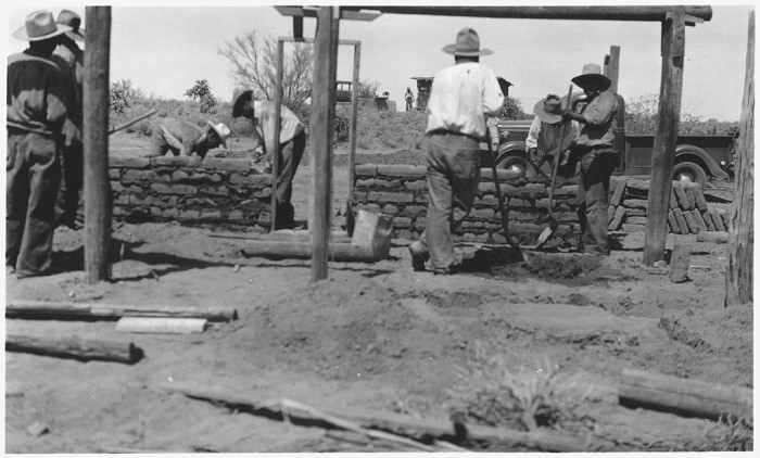 11. This out of focus photo shows a group of Tohono O'odham men constructing an adobe building.