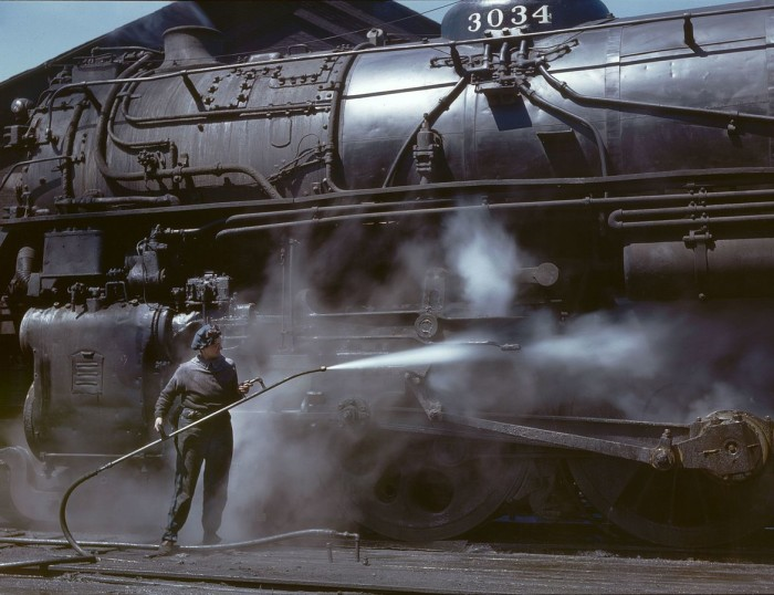 2. Mrs. Viola Sievers, one of the wipers at the roundhouse, gives this train a bath of live steam in Clinton during the early 1950s.