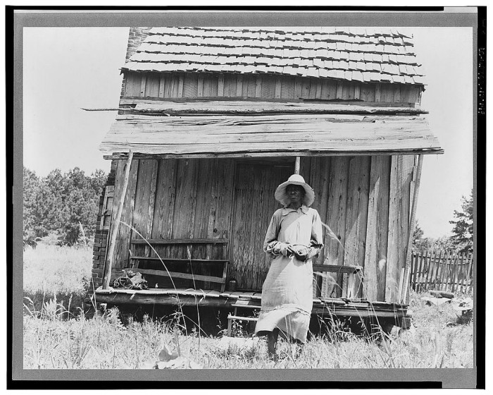 12. During the summer of 1937, a sharecropper's wife is photographed in front of her home.