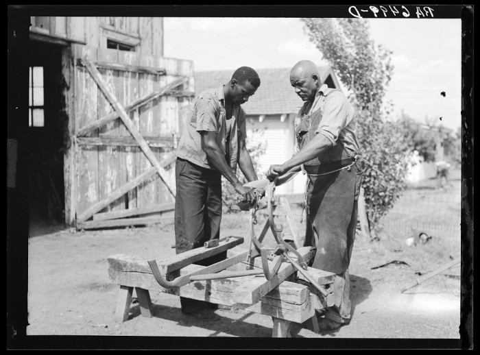 """12. Two men on a Sunflower plantation work to repair a """"double shovel"""" cultivator."""