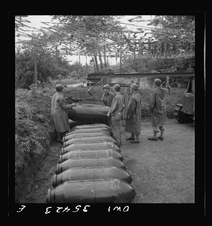 16. Soldiers at the Greenville Army Airbase in Greenville, SC move 2,000 lb bombs out of the revetment area in 1943.