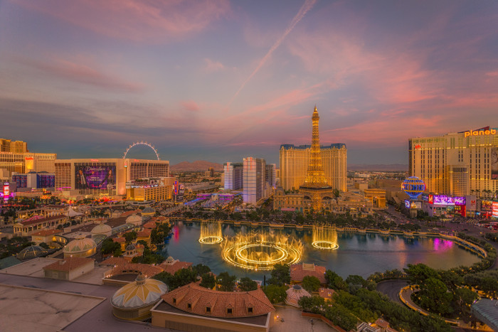 10. A gorgeous view of the Bellagio fountain show at dusk, with the Las Vegas Strip skyline in the background.
