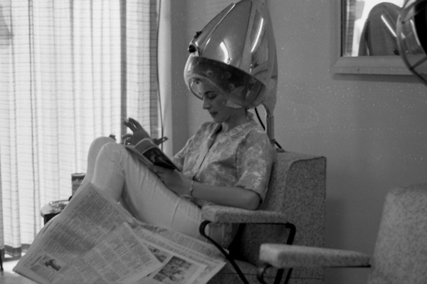 17. Popular hair styles required a lot more upkeep back in the day.  Pictured is a woman waiting under a hair dryer in a beauty shop in Tallahassee.