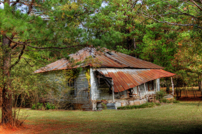 """14. Titled """"Sit A Spell,"""" this abandoned house is located in Fort Rucker, Alabama. Notice the chairs on the front porch?"""