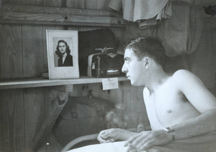 3. A Soldier from Texas admires a photo in a frame above his bunk at Columbia Army Air Base. 1941.