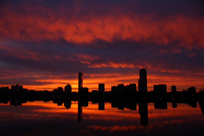 7. Boston is reflected in the fiery waters of the harbor.
