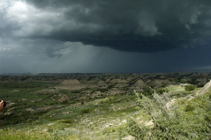 3. A dark, threatening storm casting a shadow over a beautiful landscape