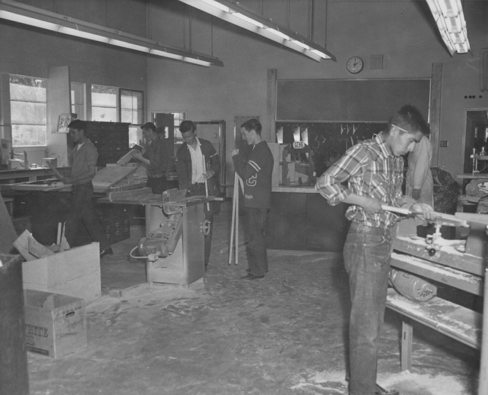 14. Meanwhile, these boys are participating in a wood shop class at the same high school.