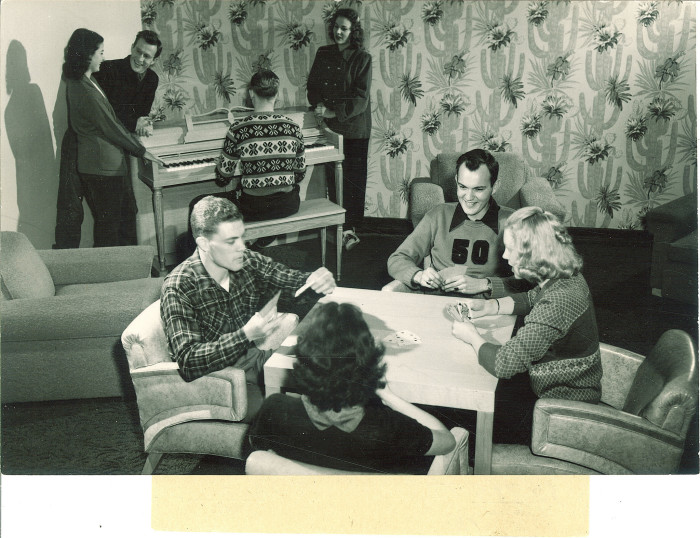 6. These college students in the 1960s sit down for a friendly game of cards on a Friday night.