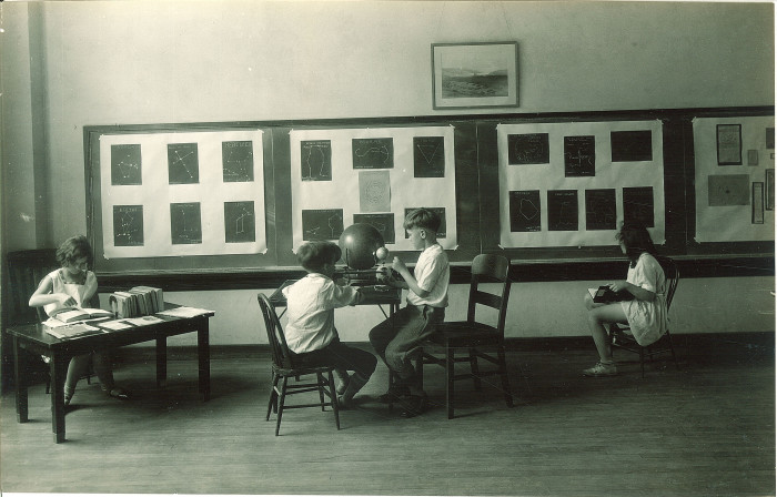 9. These elementary school students in Iowa City study astronomy for the school open house in 1930.
