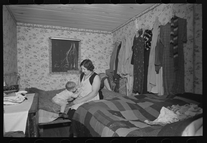 1. A mother and child sit together in a crowded bedroom at a house in Clay County. A husband, wife, seven children, and a grandchild all lived together in the house.