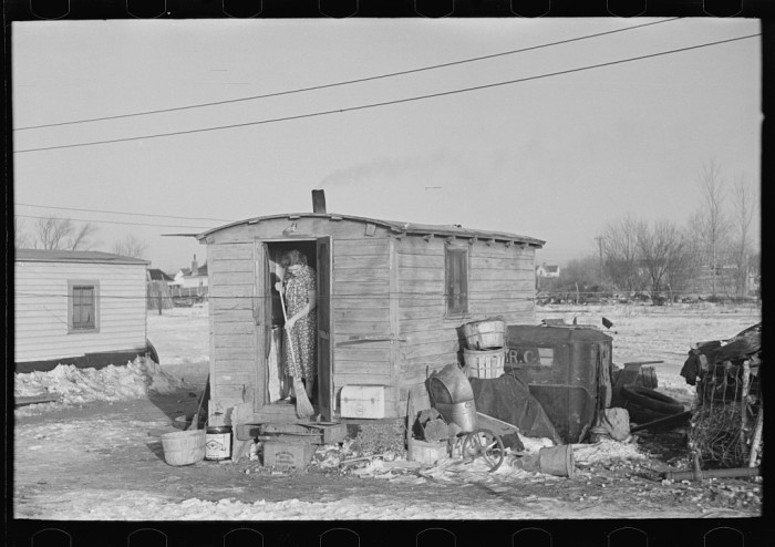 """3. A woman sweeps the steps of her shack in """"Shantytown."""""""