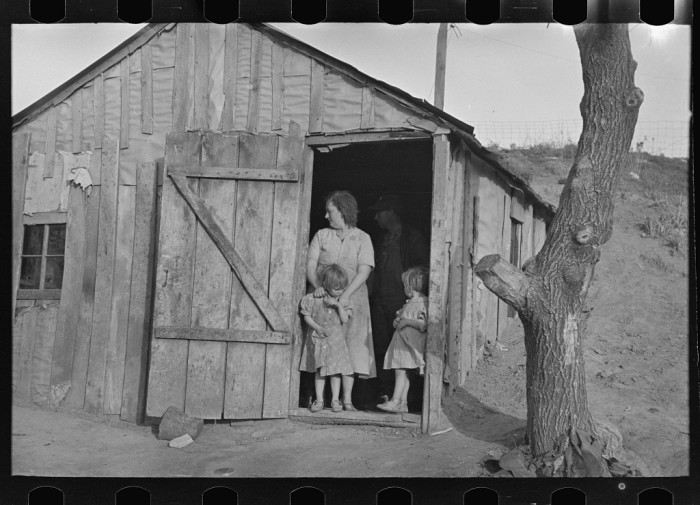 6. A woman and her children stand in the doorway of their home near Smithland, where she and her husband work as tenant farmers.