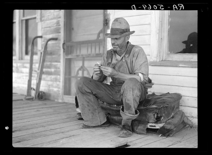 """2. """"Waiting for better times, J. Huffman of Grassy Butte, North Dakota, sits in front of his closed store"""""""