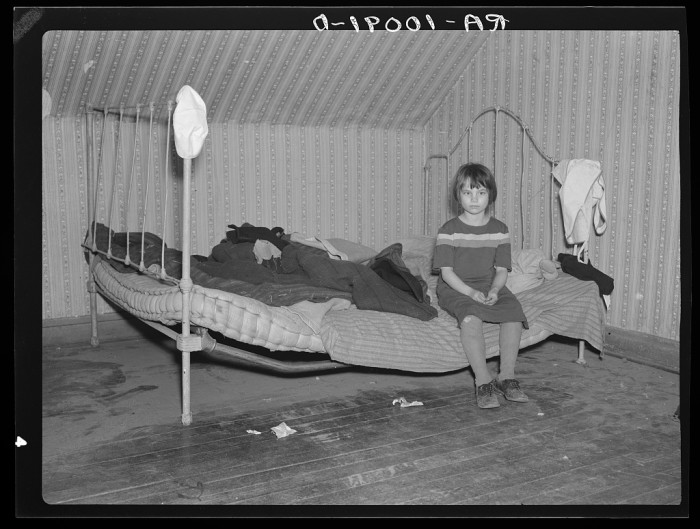 9. A young girl from Milford sits on a makeshift bed she shares with her siblings. There are no sheets, pillowcases, or pillows, and the bedding consists of castoff rags and a few old blankets.