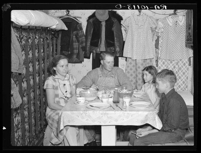 10. A man and his family eat dinner together in shack that he built himself. The man worked as a hired hand, and managed to save enough to make a partial payment on seven and a half acres of land near Spencer.