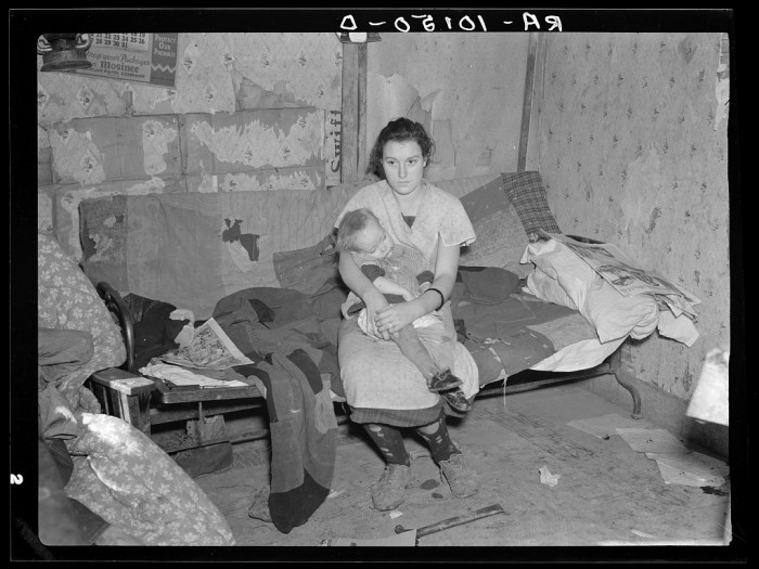 12. The daughter of a hired hand in Ringgold County sits on a makeshift couch stuffed with blankets and rags.