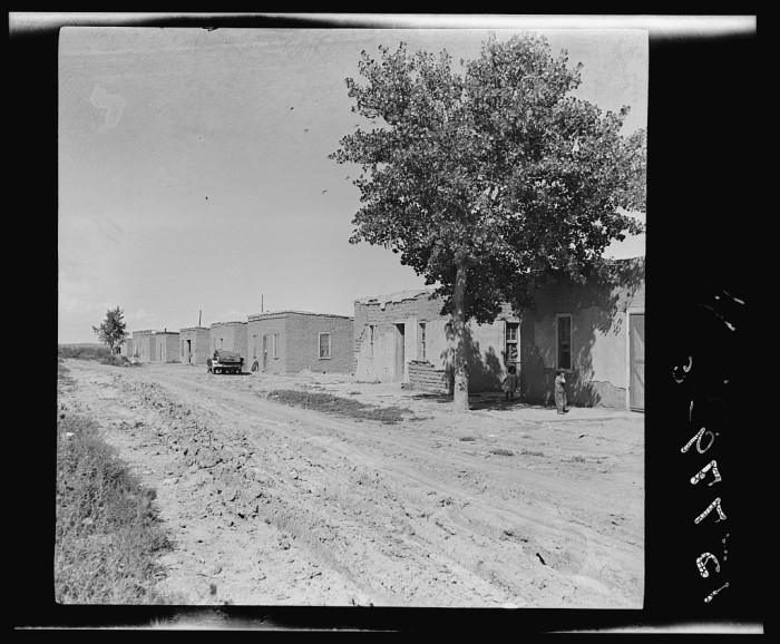 """1. """"A colony of twenty adobe houses built by the inhabitants with materials supplied by the Great Western Sugar Company. Thirteen of the houses are used, seven being unfit for habitation. In the thirteen houses, there live approximately fifty people. Being in limits of an incorporated town (Hudson) there is a water system. However, there is only one outlet (an outdoor spigot) for this whole colony. No electricity, gas or sewerage system."""""""