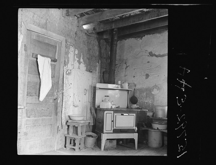 """6. """"Kitchen with stove bought last winter from Denver salesman. Great Western Sugar Company's beet sugar workers colony at Hudson, Colorado. The housewife says, """"The man told me it would save its cost in food, but the roof leaks so bad it's getting all rusted up.  (Notice hole in adobe wall above stove; this stove cost the earnings of about three months' work of all the workers in this family.)"""""""
