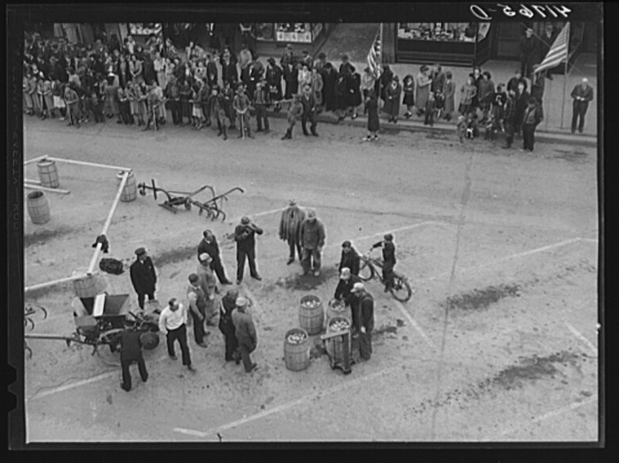 13. Weighing barrels of potatoes for the benefit of newsreel cameramen documenting the event.