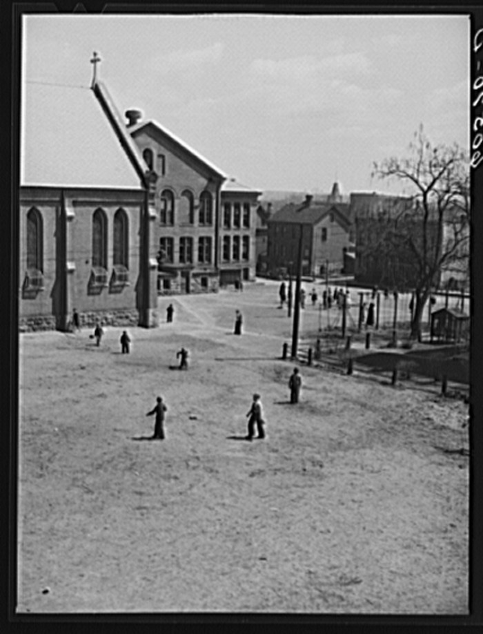 4. These children from a Catholic school in Dubuque take a break for recess, and run around in the churchyard.