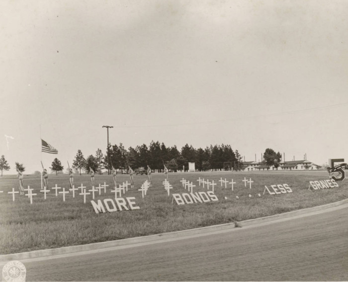 """9. A photo of the promotional display for the 5th War Bond Rally in 1944 touts """"More Bonds - Less Graves"""" as the slogan."""