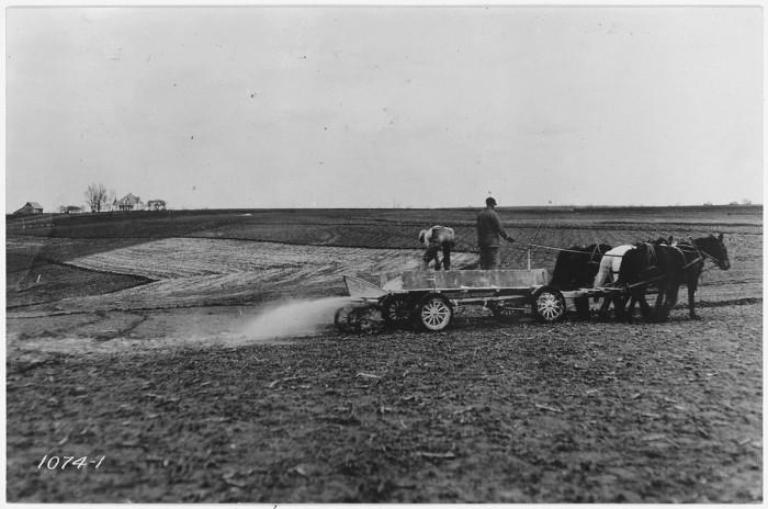 9.Man using team and wagon to spread fertilizer.