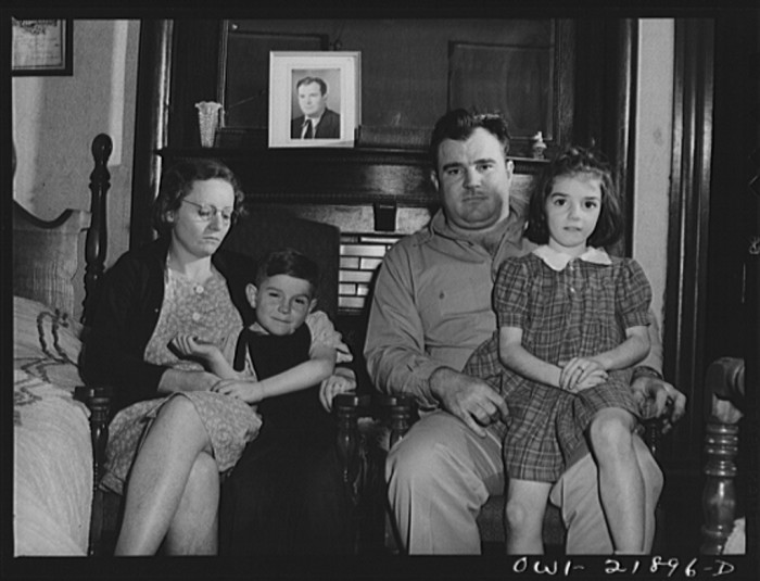 17. Marvin Johnson, a truck driver from Montgomery, is sitting with his wife and children for a family photo - March 1943.