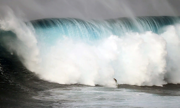 11) Can you spot the surfer among this monstrous wave?