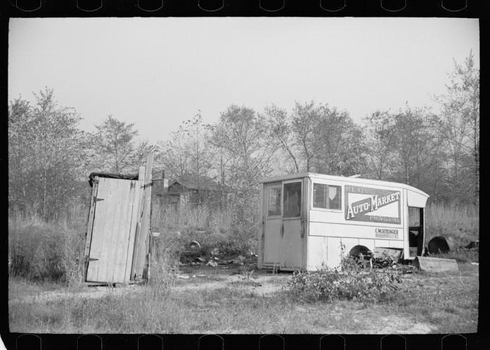 13. Mill workers call this abandoned truck body and neighboring outhouse home. Millville, 1938.