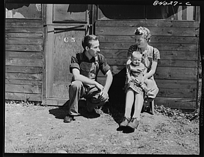 16. A young family sits outside their makeshift home at the Timberville farm labor camp, 1942.