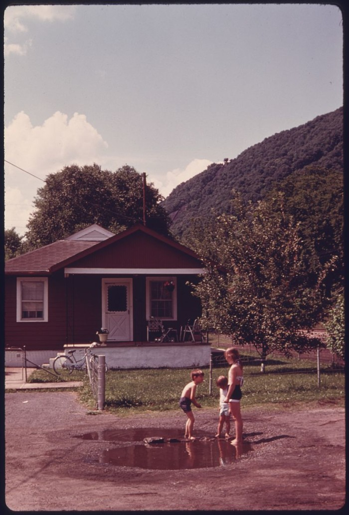 2. Children play in a puddle in a neighborhood in Boomer in June 1975.