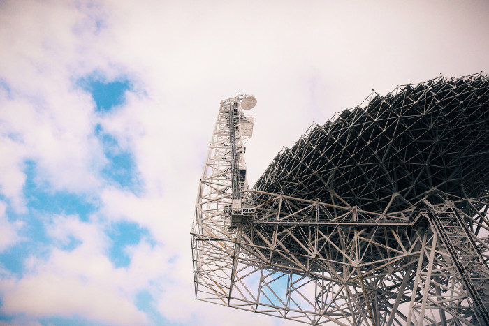 The telescope can hear sounds from millions of miles away. Cell phones would drown out that sounds, which is why they are prohibited.