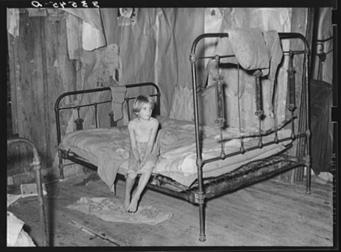 10. This little girl is the daughter of an agricultural day laborer. She is sitting on a bed in a bedroom of her home in McIntosh County.