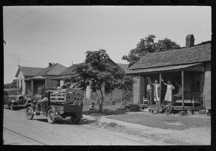 15. A friendly family waving goodbye from their porch to a family bound for California from Muskogee.