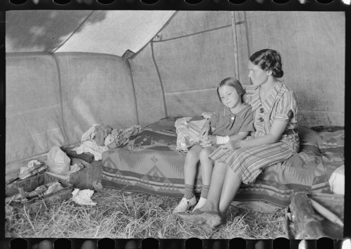 4. A mother and daughter inside their tent on the banks of the Arkansas River in Muskogee County.