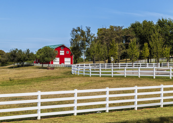 12. A classic red barn and white picket fence in the country.