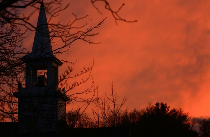 9. A glowing orange sky churns behind the spire of a Cape Cod church.