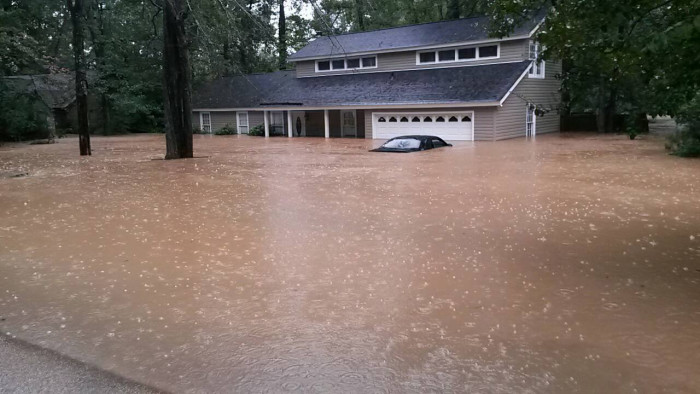 3. Rising waters nearly cover the car in this family's driveway and have nearly filled the first floor of the home.