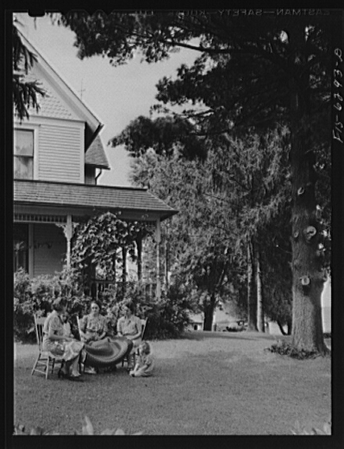 9. This was the home of E.J. Saugstad. Mrs. Saugstad and neighbors braid rugs in front of the Vernon County home.